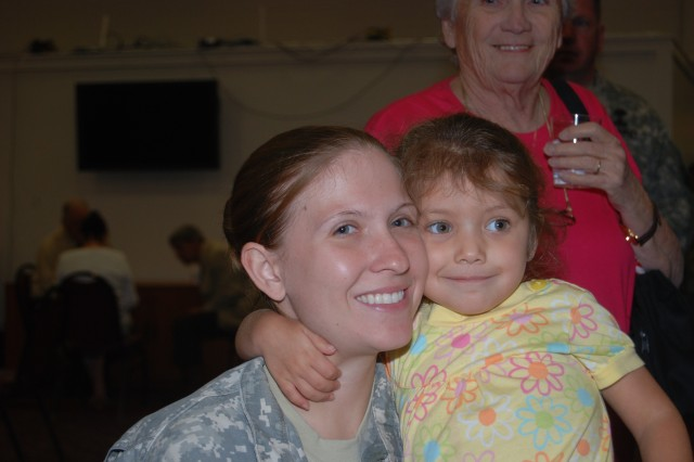 """Shylah Prewitt, 3 years old, hugs her mother Spc. Jessica Prewitt, 440th Blood Detachment, following the deployment ceremony at the Roadrunner Community Center April 19. When asked where her mother was going Shylah said, """"She is going to Afghanistan because the people are in trouble, she is going to put people in time out."""""""