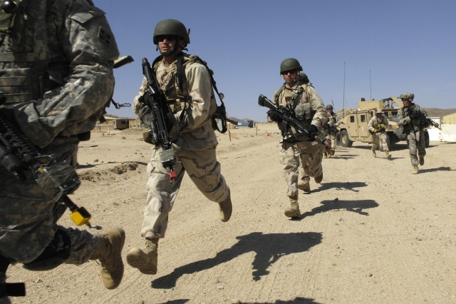 Soldiers head toward a simulated Iraqi village during training against opposing forces at the National Training Center at Fort Irwin, Calif.  Simulated IEDs, role-playing villagers -- even Hollywood make-up artists, make the pre-deployment training here as realistic as possible.