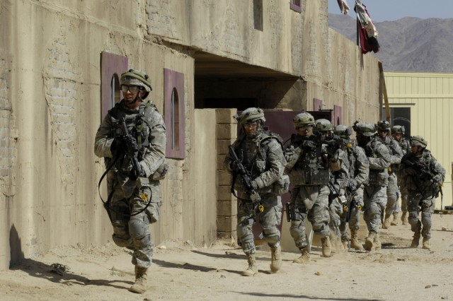 Soldiers maneuver through a simulated Iraqi Village against opposing forces to gain 'real world' training in urban operations.  The Fort Carson, Colo.-based Soldiers from the 2nd Brigade Combat Team, 4th Infantry Division are training at the National Training Center at Fort Irwin, Calif.