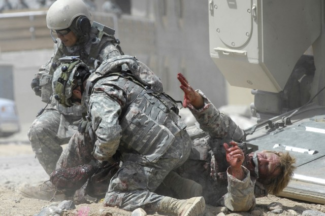 Soldiers from the 204th Base Support Battalion react to a role player injured during a simulated improvised explosive device detonation.  The 4th Infantry Division Soldiers are training at the National Training Center, Fort Irwin, Calif.