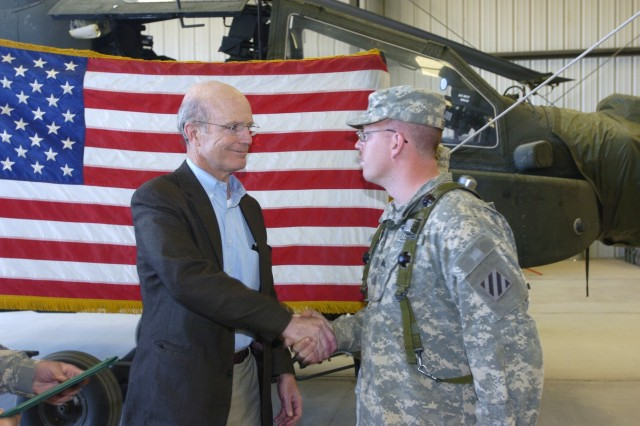Secretary of the Army, the Honorable Pete Geren shakes hands with Sergeant Greg A. Freeman after Freeman reenlisted during his training rotation at the National Training Center and Fort Irwin. Freeman's unit is preparing to deploy in support of Operation Iraqi Freedom.
