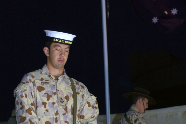 Leading Seaman Shane Perry stands mounted on the cenotaph with three other Catafalque Party members as an honor guard for their brothers and sisters lost in combat during a dawn Anzac Day ceremony April 25 at the Roundhouse on Camp Victory.