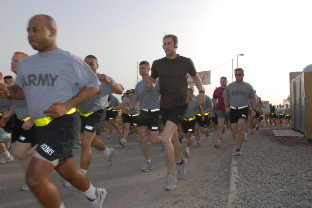 "Servicemembers launch from the starting point during the Army Reserve's 100th birthday 5k run.  ""Thanks for being here and supporting our mission,"" said Brig. Gen. Robert Hipwell, commanding general, Task Force North, 300th Military Police"