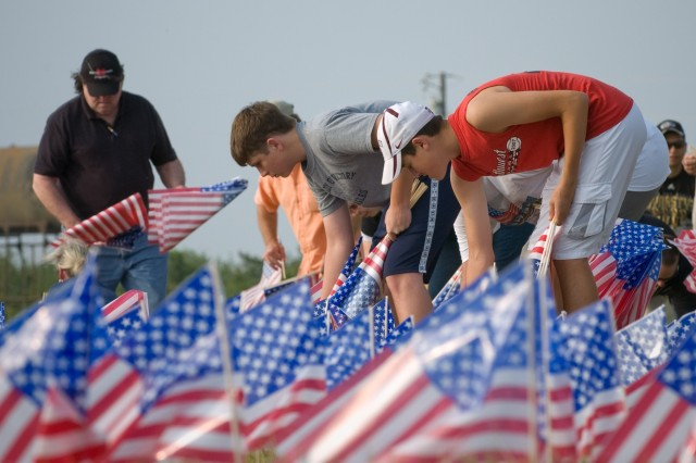 Howard Mitte (peach shirt), Clayton Mitte (gray shirt), Brayden Blanton (red shirt), set 4001 flags in the grass near the Port O'Connor Community Center in Texas, on May 2, before Warrior's Weekend began. The flags commemorate the servicemen and women who gave their lives in the war on terror.