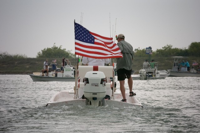 A boat owner and assistant motor off with a wounded warrior ready to go fishing during Warrior's Weekend in Port O'Connor, Texas, May 3. More than 125 wounded warriors and their Families from Brooke Army Medical Center, Walter Reed Army Medical Center, Fort Hood, Texas, and Fort Bragg, N.C., participated in the fishing tournament. About 135 local fishermen volunteered their time and boats to take the Soldiers out on the Gulf of Mexico.