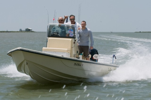 A Soldier and local fishermen head back to dock after a day of fishing on the Gulf of Mexico off of Port OAca,!a,,cConnor, Texas, during WarriorAca,!a,,cs Weekend, May 3.