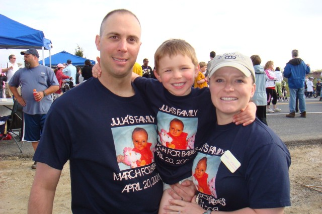 """Staff Sgt. Wendy Spohn and Sgt. 1st Class Stephen Spohn, both with the Army Materiel Command Band, with their son Lukas at the March of Dimes walk April 20. The family is wearing t-shirts saying """"Julia's Family"""" in memory of their 4-month old daughter who passed last year."""