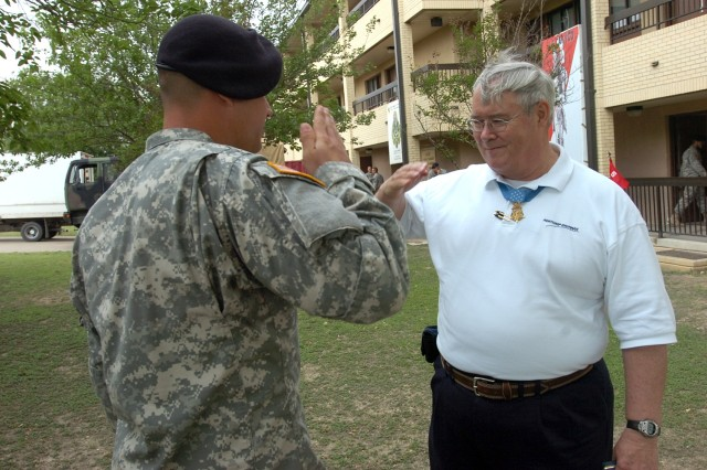 Medal of Honor recipient Charles Hagemeister salutes Spc. Jeremy Varnell, a medic from his former unit, Headquarters and Headquarters Company, 1st Battalion, 5th Cavalry Regiment, 2nd Brigade Combat Team, 1st Cavalry Division, during his visit with the Black Jack troops May 1.