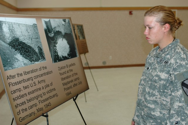 Birmingham, Ala., native Spc. Kristina Hunter, a fueler from 1st Battalion, 227th Aviation Regiment, 1st Air Cavalry Brigade, looks at a photo exhibit at the Days of Remembrance observance April 30 at Fort Hood, Texas. Hunter's great-great aunt and uncle immigrated to the United States in the 1930s to escape the Holocaust.
