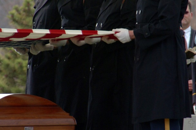 Casket Team members reverently lift the nation's colors from a Soldier's casket to start the ceremonial flag-folding.