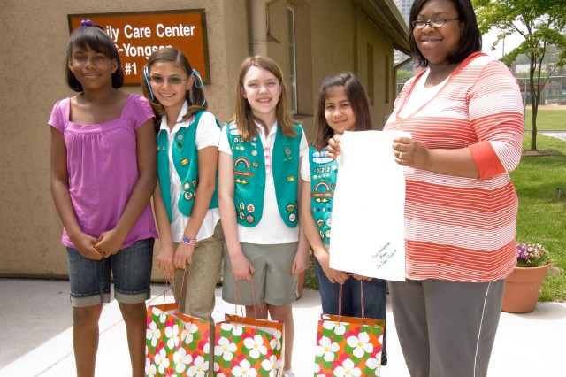 YONGSAN GARRISON, Republic of Korea - Junior Troop 22 Girl Scouts present expectant mother Phaedra King with blankets and burp cloths at the Family Care Center May 2. The Girls Scouts are (left to right) Kayla Putman, Isabell Murray, Gabi Moreau and Allie Rios.