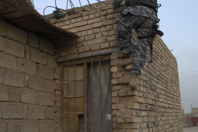 A Soldier with the National Police Transition Team climbs a building to search for weapons caches in Jisr Diyala, Iraq.