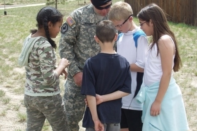 Sgt. 1st Class Dustin Swinney guides a group of students from Odyssey Elementary School through a navigation course.