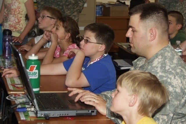 Fourth grade students from Odyssey Elementary School in Colorado Springs, Colo., watch intently as Sgt. Tony Lopes shows them a 3-dimension orbital pattern of the GPS constellation.