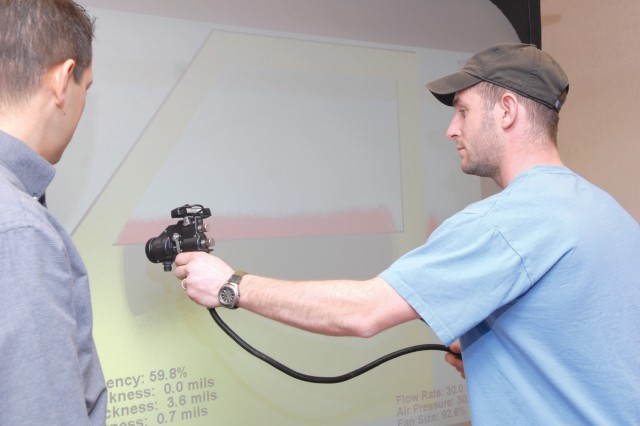 Carmelo Rivera, left, teaches Joseph Limani how to use the Virtual Paint System. The system is designed to improve painters' technique and consistency.