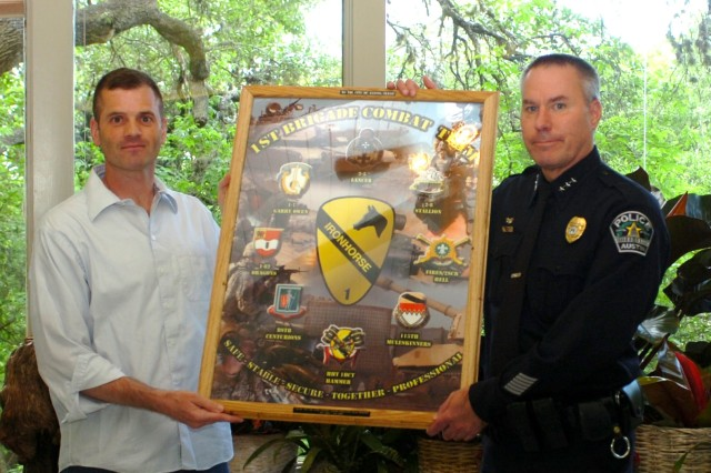 """David Carter (right), chief of staff for the Austin Police Department, accepts a framed and engraved 1st """"Ironhorse"""" Brigade Combat Team, 1st Cavalry Division poster on behalf of the Austin city government from Lt. Col. John Cook, executive officer, 1st BCT, 1st Cav. Div. April 30 during an informal ceremony in Austin recognizing the city government's contributions to the Ironhorse Brigade's reconstruction efforts in Iraq."""