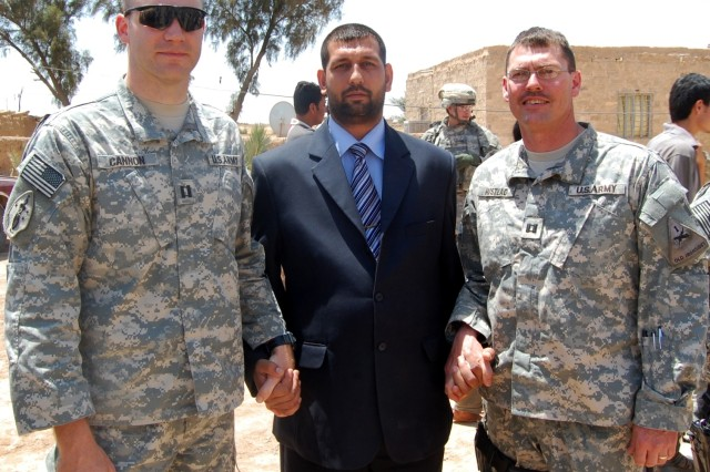 (Left to right) Capt. Charles Cannon, commander of Battery A, 1st Battalion, 10th Field Artillery, Qussin Yassim, leader of the Tessah Nissan Sons of Iraq group, and Capt. Matthew Hustead of U.S. Army Europe's 4th Battalion, 27th Field Artillery, join hands in a symbolic gesture of the continued bond between the SoI and coalition forces after a farewell ceremony for the departing 1-10th at Tessah Nissan, Iraq, May 1. The recently arrived 4-27th will continue the mission the 1-10th performed during its deployment in support of Operation Iraqi Freedom
