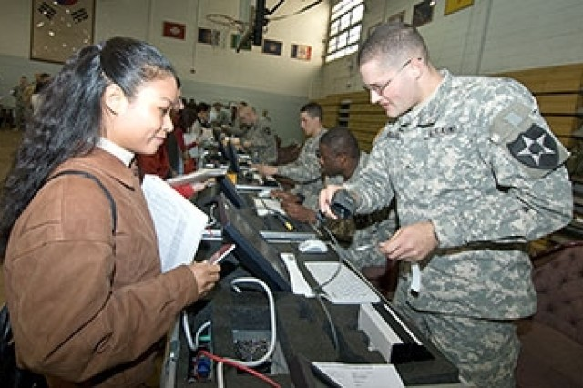YONGSAN GARRISON, Republic of Korea - Pvt. Justin Ahlers (right) makes sure that Nix Hataitip's family information is current in the NEO tracking database during the last Noncombatant Evacuation Operation exercise in November 2007. The next exercise, a semi-annual event Courageous Channel, is May 15-18, 2008, at Yongsan's Collier Field House.