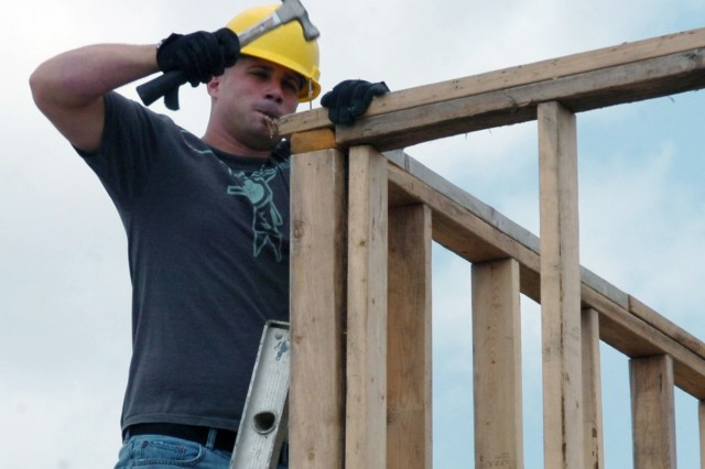 """Austin native Spc. James Smith, an engineer with Company E, 2nd """"Stallion"""" Battalion, 8th Cavalry Regiment, hammers nails into a frame May 1 which makes up part of a new shed that will store equipment for the Habitat for Humanity organization in Killeen, Texas."""