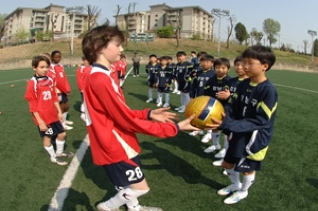 USAG-YONGSAN, SOUTH KOREA - Mathieu (Matt) Gosselin, Eighth Army Youth Good Neighbor Soccer Team, presents a signed team ball to the Gangnam team's captain prior to the start of the April 19 soccer match. This was the GNP youth soccer team's second match, played on new artificial turf fields at USAG-Yongsan, since the team was started. - U.S. Army Photo By Edward Johnson