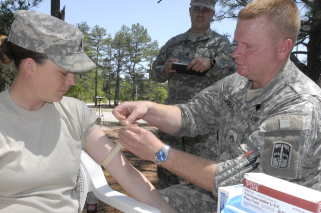 Staff Sgt. Clint Campbell, Company C, Task Force Marshall, prepares to perform an IV saline lock on Staff Sgt. Nicole Simonson April 29 during the 2008 Fort Jackson Drill Sergeant of the Year Competition. The grader is Staff Sgt. Brian Lewis, a medic assigned to the 193rd Infantry Brigade.