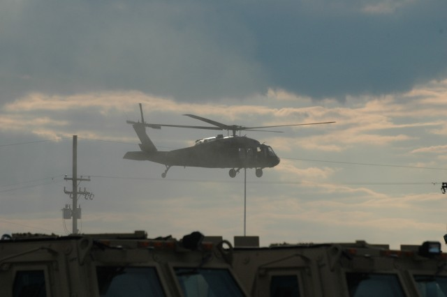 Black Hawk helicopters fly into the staging area at seaport Charleston before loading onto a cargo ship.