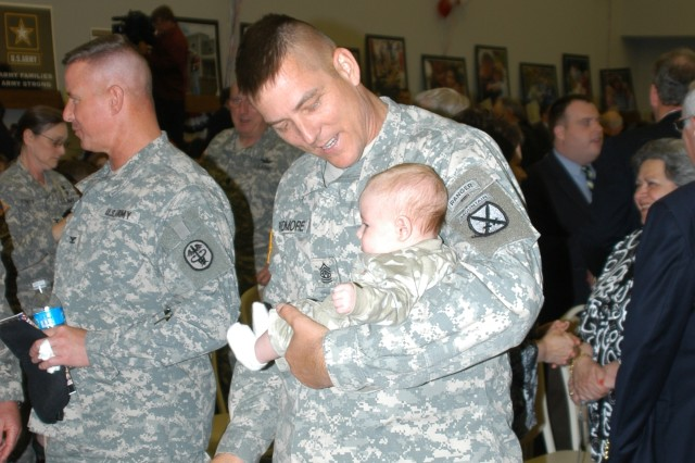Sgt. Maj. James Redmore of 10th Mountain Division Command cradles a baby prior to the signing of the Army Community Covenant in Watertown, N.Y. Army Secretary Pete Geren visited northern New York May 9, 2008, to participate in the signing of the Army Community Covenant signifying the commitment of the local community to continue its tradition of strong support to Fort Drum Soldiers and their Families.