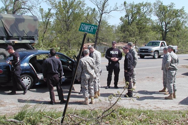 Five members of the Missouri National Guard 203rd Engineer Battalion coordinate with volunteer officers from the Benbrook, Texas, Police Department for traffic control and security efforts in Granby, Mo., after a tornado left a mile-wide path of destruction across Newton County, Saturday. The Soldiers are Pfc. Sampson, Sgt. Byers, Staff Sgt. Dickens, Pfc. Anderson and Sgt. Bousquet, all of the 294th Company in Carthage.