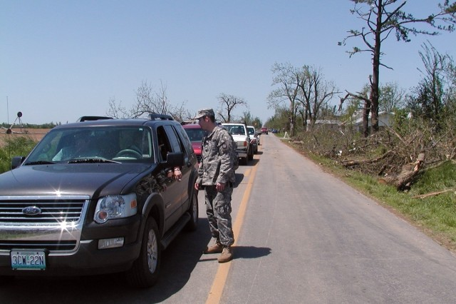 Spc. Russell Fenno with the Missouri National Guard Forward Support Company, 203rd Engineer Battalion directs traffic around a heavily affected area in Newtonia, Mo., after a tornado destroyed dozens of structures and uprooted hundreds of trees on Saturday.