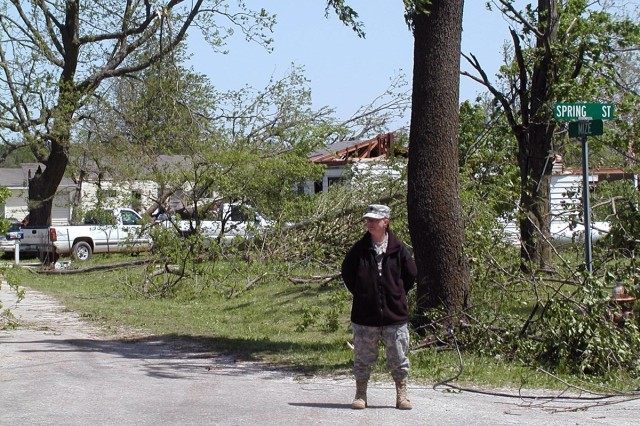 Spc. Rhonda Fleming with the Missouri National Guard Forward Support Company, 203rd Engineer Battalion guards the entrance of a Newtonia neighborhood completely devastated by a tornado that left a nine-mile long path of destruction in Newton County, Mo., on Saturday.