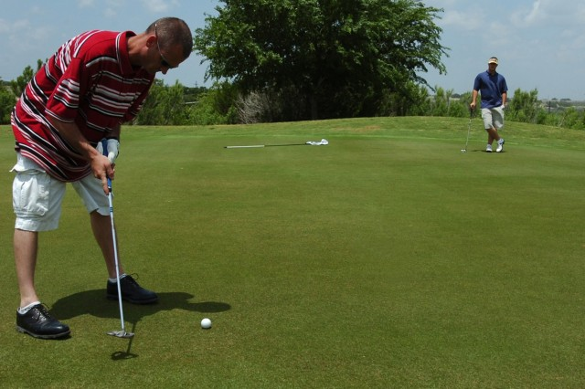 Sgt. Curtis Young, assigned to 15th Brigade Support Battalion, 2nd Brigade Combat Team, 1st Cavalry Division gets ready to putt, while Spc. Morgan McGough, also with 15th BSB, looks on. Young and Curtis were taking part in the Black Jack Golf Scramble May 7 at the Clear Creek Golf Course on Fort Hood.