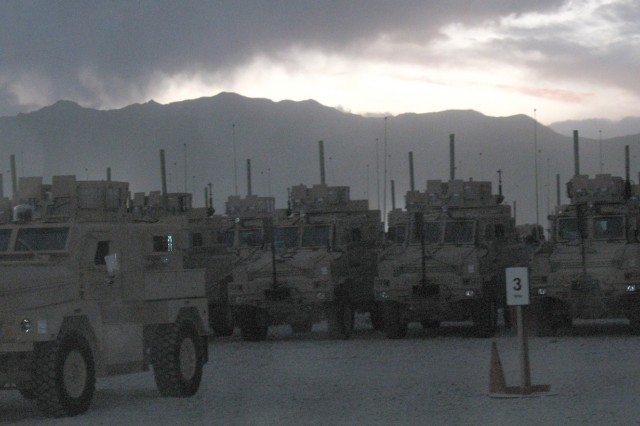 As the light fades, Friday, May 9, at Bagram Airfield, Afghanistan, Mine Resistant Ambush Protected vehicles awaiting issue, by 401st Army Field Support Brigade, to Warfighters in Operation Enduring Freedom are silhouetted against the distant Hindu Kush mountain range.