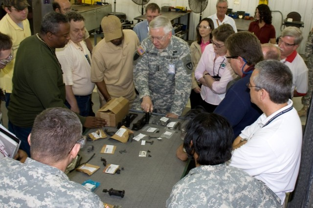 Lt. Gen. William Mortensen, deputy commanding general at the Army Materiel Command, makes a site visit to Anniston Army Depot. Here, he discusses supply chain management with depot and Defense Logistics Agency personnel in the small arms repair facility over a table of M2 machine gun parts.
