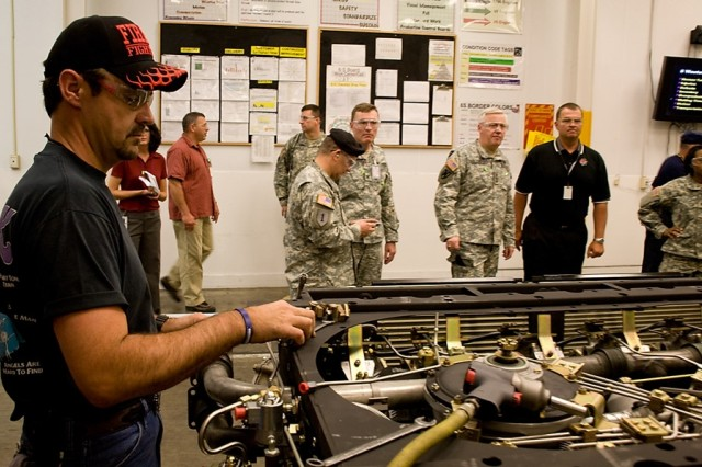 Anniston Army Depot mechanic Mack Ford works on a reciprocating engine as Army Materiel Command visitors look at process improvements made in the depot\'s production line.