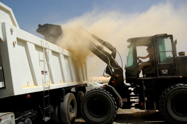 "Equipment Operator Construction Man (EOCN) Jeremiah Johnson, Naval Mobile Construction Battalion 74 dumps a load of debris from the paving project fronting the Army Materiel Command ""Wilson Willows"" housing area at Camp Arifjan, Kuwait, April 23.  Paving continues in the Zone 6 area of the camp, and everyone traveling through the zone should exercise patience, and maintain situational awareness, as the long-awaited upgrade moves forward."