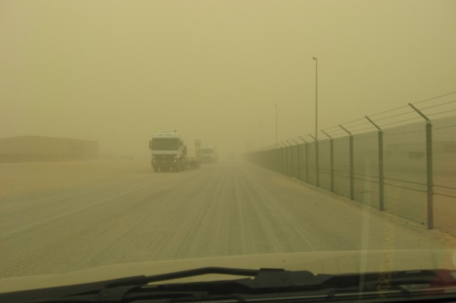 Midday turns dusk-like, Apr. 9, 2008, as a sandstorm engulfs vehicles traveling a side road on Camp Arifjan, Kuwait.