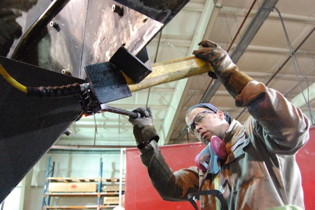 "David Meulenberg, General Dynamics Land Systems Division, performs body repair work on a Stryker combat vehicle at the 1st Battalion, 401st Army Field Support Brigade Stryker Battle Damage Repair Facility at Camp As Sayliyah, Qatar.  Tim Armstrong, GDLSD-Qatar site manager, says ""we feel we're doing our part in the war. A lot of our guys have served (in uniform) - some haven't. Here we all feel like we're contributing."""