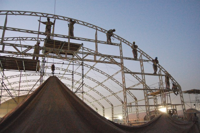 As darkness falls, workers install a fabric end section on a new maintenance tent at Camp Arifjan, Kuwait, Apr. 21, 2008.  The tents are one way to protect Soldiers and civilians from the sun, wind, dust and high temperatures of the Arabian Peninsula.