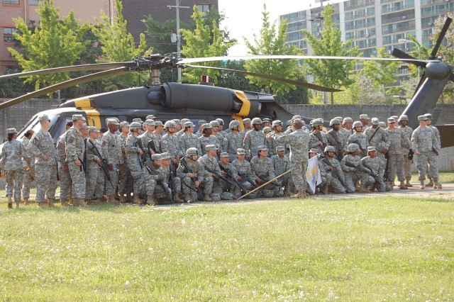 176th Finance Company Soldiers pose in front of a 2nd Battalion, 2nd Aviation Regiment UH-60 Black Hawk at the completion of a three-day training exercise at Camp Market.