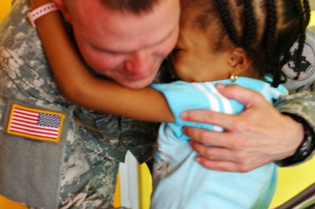 Maj. Kevin Pruitt, information officer team chief from the 49th Theater Information Operations out of Austin, Texas, gets a hug from 8-year-old Ariana Peters at Mount Hope Hospital, Trinidad. Major Pruitt was here in support of Beyond the Horizon, a joint humanitarian training mission, when he donated blood to help save Ariana's life.