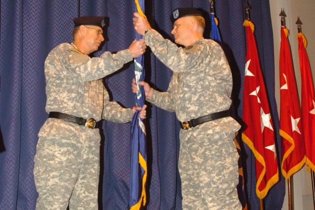 Gen. Benjamin S. Griffin, commander, U.S. Army Materiel Command, passes the Military Surface Deployment and Distribution Command colors to Brig. Gen. Brian R. Layer, acting commander of SDDC, during a change of command ceremony at U.S. Transportation Command headquarters.
