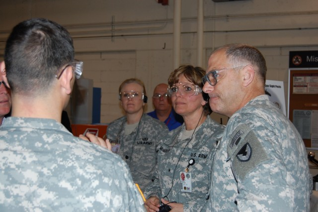 """Brig. Gen. Patricia E. McQuistion, Defense Supply Center Columbus commander, second from right, Col. Craig S. Cotter, Joint Manufacturing and Technology Center commander, far right, Col. Steven Bianco, DSCC land supplier operations director, and Lt. Col. Mary """"Crickett"""" LeMasters, Defense Logistics Agency customer service representative, TACOM LCMC Rock Island, stop for a discussion during a tour of the JMTC May 1."""