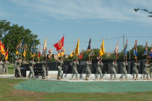 The unit colors of the 1st Cavalry Division make their way around the division's Operation Iraqi Freedom memorial to begin the rededication ceremony held at Cooper Field May 16. The memorial was rededicated after having 493 names added to the black-stone monument.