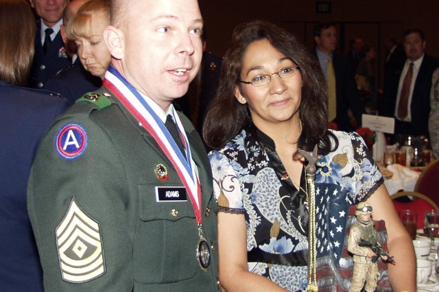 1st Sgt. Steven M. Adams, with wife Maria by his side, reacts to the news that he is selected as the Outstanding Enlisted Personnel for 2008 in Category Three: E-7 and E-8 during the annual Armed Forces Luncheon held at The Broadmoor Hall, Colorado Springs, Colo, on May 16. Adams is the first SMDC/ARSTRAT Soldier to win this coveted honor. First sergeant of the 1st Space Company, 1st Space Battalion, Adams beat out three other Air Force enlisted personnel in the category. The Colorado Springs Armed Forces Week Awards Luncheon honors enlisted men and women and provides a unique opportunity to express the community's gratitude for their dedication and service to the nation.