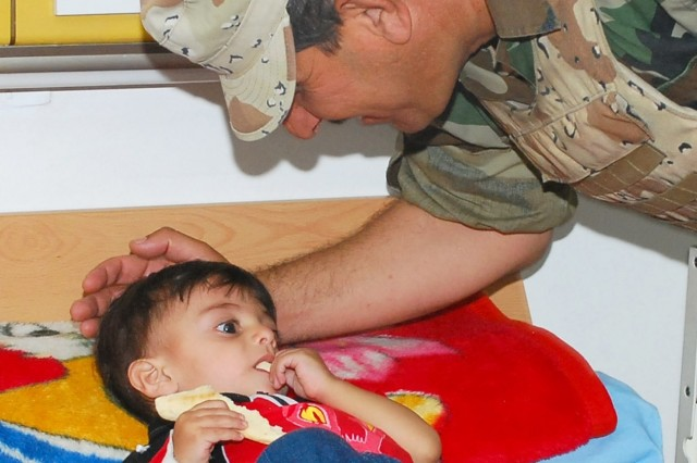 1st Lt. Arkan Abraheem Ali, who serves as the executive officer of the 3rd Company, 1st Battalion, 54th Brigade, 6th Iraqi Army Division, says hello to a young Iraqi child being treated for cancer at the Iskan Children's Teaching Hospital in Mansour, a district in western Baghdad, May 15. Ali and soldiers in his company visited the hospital with Soldiers from the 2nd Brigade Combat Team, 3rd Infantry Division, currently attached to the 2nd Brigade Combat Team, 101st Airborne Division (Air Assault), Multi-National Division - Baghdad, to pass treats to the children. Missions such as this help the IA and MND-B Soldiers to interact more closely with the community they operate in.