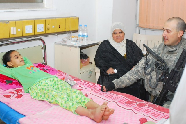 Staff Sgt. Anthony Orosz speaks with a young Iraqi girl being treated for cancer at the Iskan Children's Teaching Hospital in Mansour, a district in western Baghdad, May 15. Orosz and his platoon were visiting the hospital along with Iraqi Army soldiers to bring treats sent by Family members of Soldiers in his platoon.
