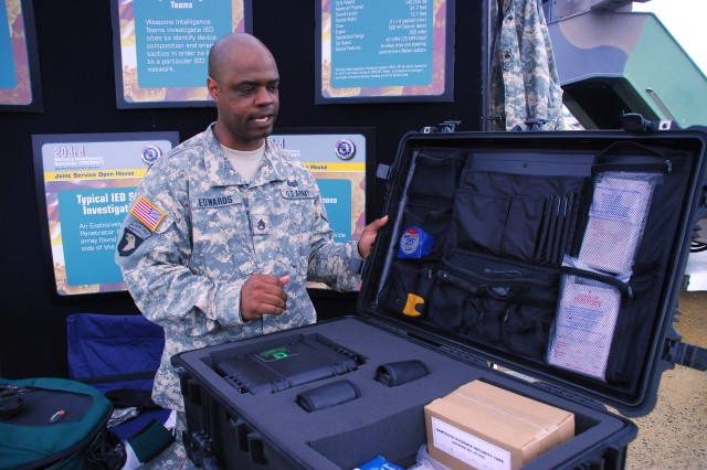 Staff Sgt. Seymour Edwards talks with visitors to the Armed Forces Day Joint Service Open House at Andrews Air Force Base, Md., about forensics kits used on the battlefield.