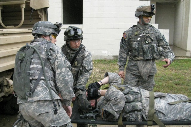 Spc. Brian Pratt (right), of Dayton, Ohio, gives a class on litter carrying and loading a vehicle during the Medical platoon training exercise at the Elijah Military Operations on Urbanized Terrain Site, May 5 and 6. Spc. Andrew Chung (middle), of Hillborough, Calif. and Pvt. Chris Clark, of Oahu, Hawaii prepare to lift a casualty into a vehicle for evacuation.