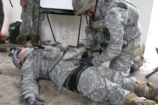 Spc. Mark Fuller (right) of Waterbury, Conn., provides care to a fellow Soldier by applying a brace to a notional broken pelvis. Dark Horse Medics trained on Evaluation and Treatment of a Casualty during platoon training exercise at the Elijah Military Operations on Urbanized Terrain Site, May 5 and 6.