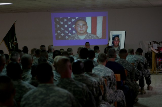 Service members watch a slide show in honor of Army Pfc. Aaron Ward during a memorial service at the chapel on Al Asad Air Base, Iraq, Friday. Pfc. Ward, 19, a military policeman with 170th Military Police Company, 504th MP Battalion, which is attached to Regimental Combat Team 5, was killed, May 6, while on a combat patrol in western Anbar province, Iraq. Pfc. Ward received military honors during the service, which included a 21-gun salute.